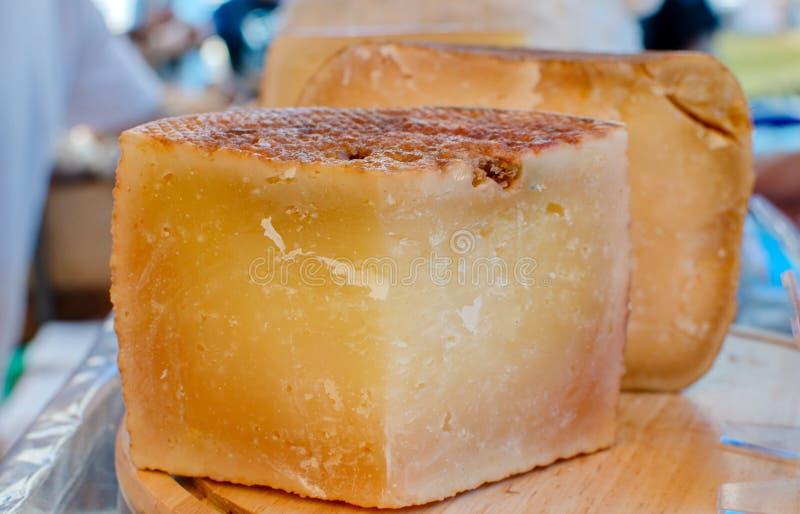 De smakelijke oude kaas van Cantal voor verkoop bij landbouwersmarkt stock foto