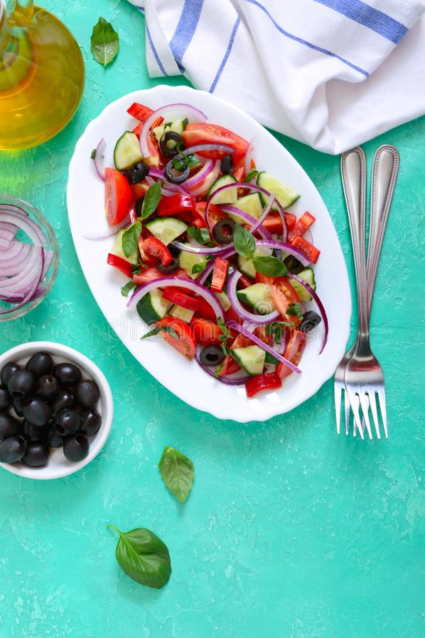De smakelijke salade van de vitamineveganist van tomaat, komkommer, rode ui, zwarte olijven, basilicumsaus op een witte plaat op  stock afbeelding