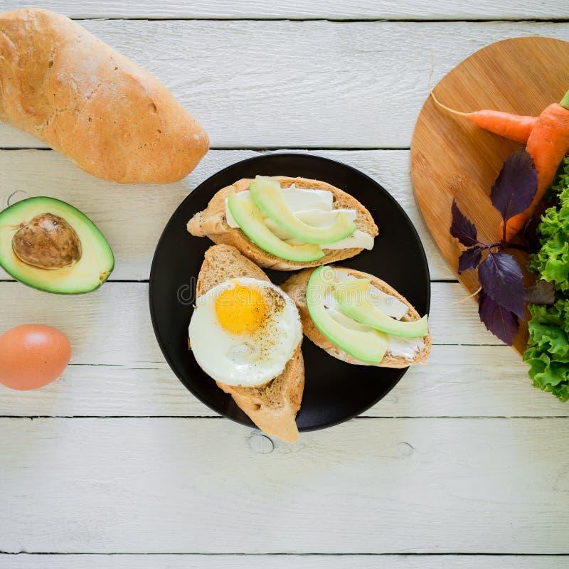 De smakelijke Sandwiches van het veganistontbijt met avocado, eieren en brood op een donkere plaat op rustieke achtergrond stock foto