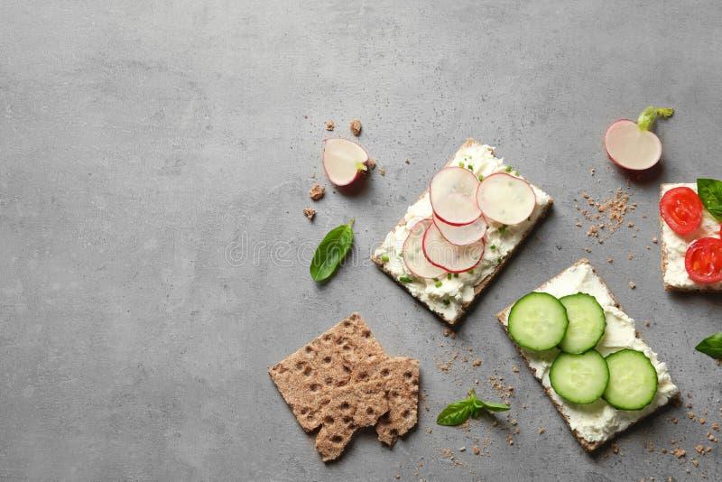 De smakelijke snacks met roomkaas en de groenten op grijze vlakke lijst, leggen stock foto's