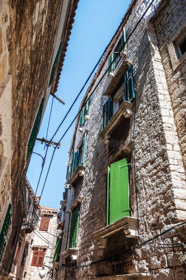 De smalle straat in de stad met oude gebouwen stock fotografie