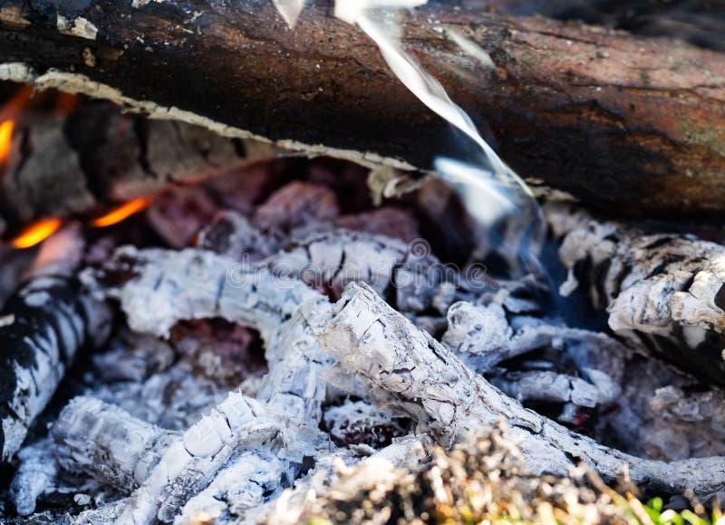 De smeulende sintels van brand met login rook, sluiten omhoog royalty-vrije stock fotografie