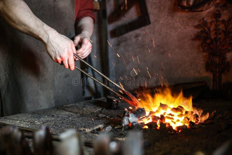de smid houdt het roodgloeiende metaal door tang in oven smeedt royalty-vrije stock afbeelding