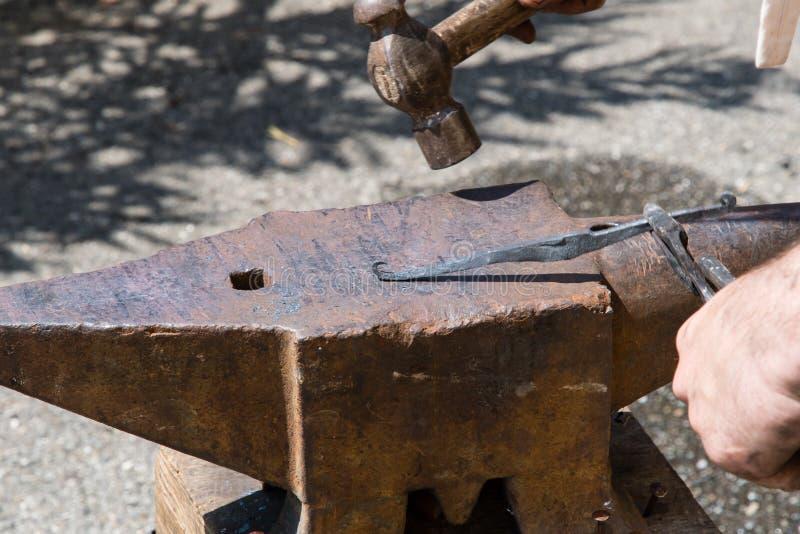 De smid werkt het ijzer met aambeeld en hamer stock foto's