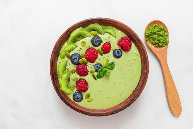 De Smoothiekom van matcha groene thee wordt gemaakt met verse bessen, noten, zaden met een lepel voor gezond veganistdieet dat on stock foto's