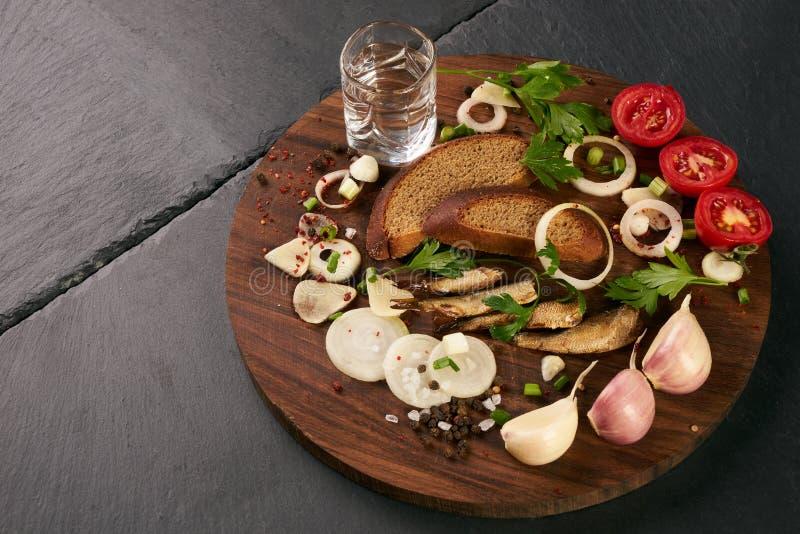 De snacks zoutten haringen met verse groenten, ui, brood, sprotten en schoten van wodka stock foto