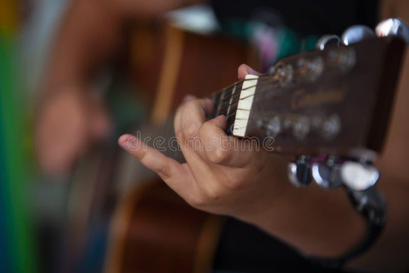 De snaren van het jongensspel op gitaar stock foto