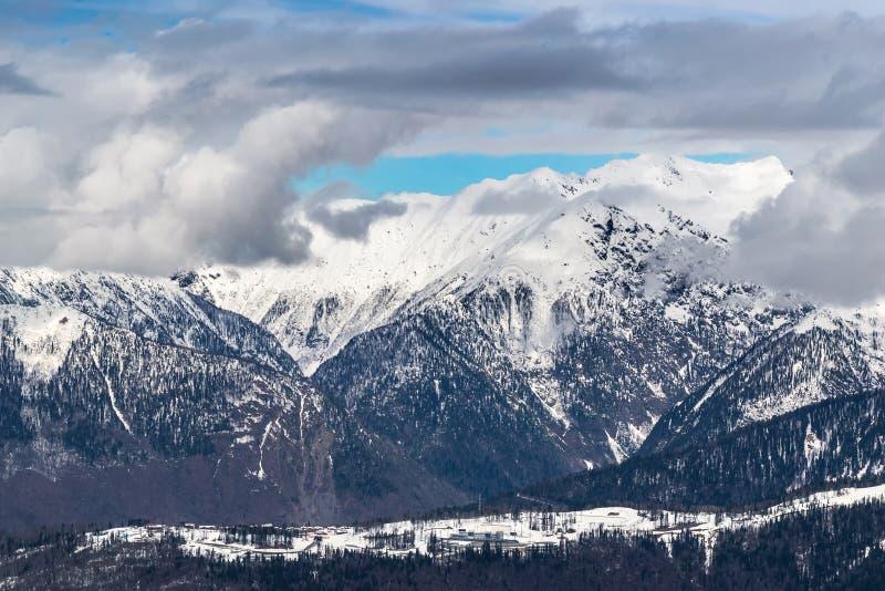 De sneeuw afgedekte bergen zijn behandeld met dikke wolken stock foto's