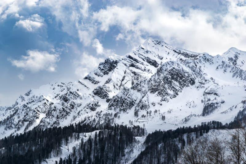 De sneeuw afgedekte bergen zijn behandeld met dikke wolken royalty-vrije stock fotografie
