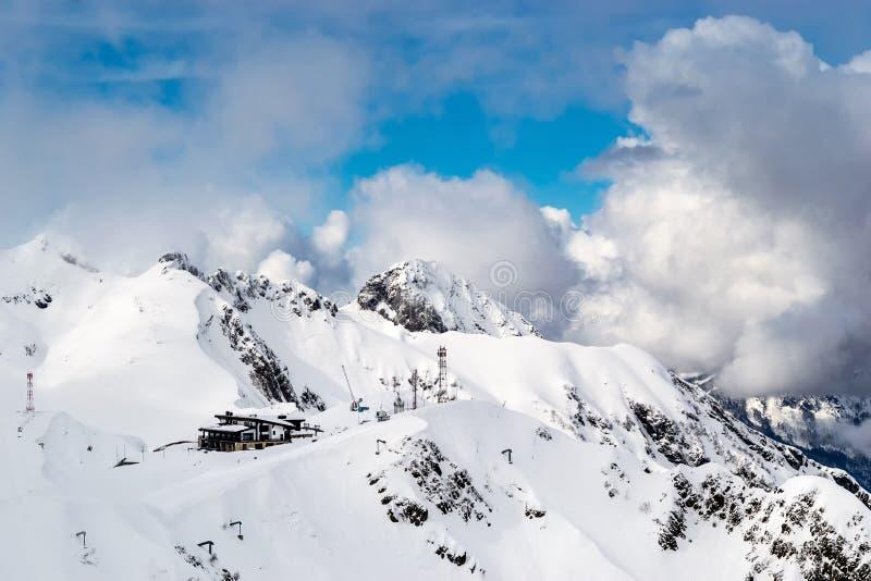 De sneeuw afgedekte bergen zijn behandeld met dikke wolken met klein blokhuis op bovenkant royalty-vrije stock foto
