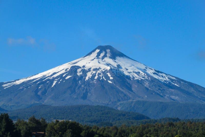 De sneeuw behandelde top van de hoogtevulkaan boven het bos royalty-vrije stock foto