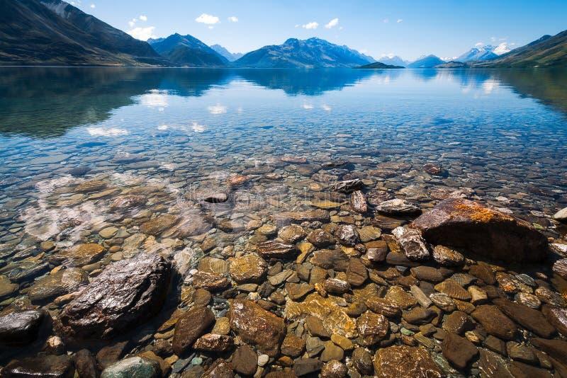 De sneeuw dekte bergenmening in de zomer van de rotsachtige kust van meer Wakatipu af royalty-vrije stock afbeeldingen