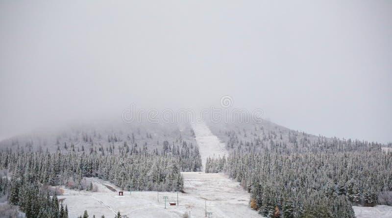 De sneeuw en de wolken verduisteren de mening over de berg Hovaerken in Zweden royalty-vrije stock foto's