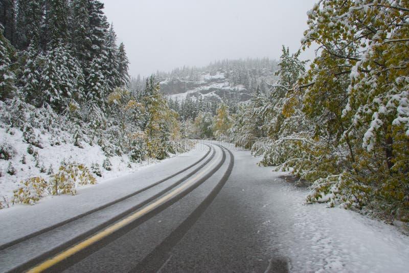 De sneeuw van de herfst op bergweg stock afbeeldingen