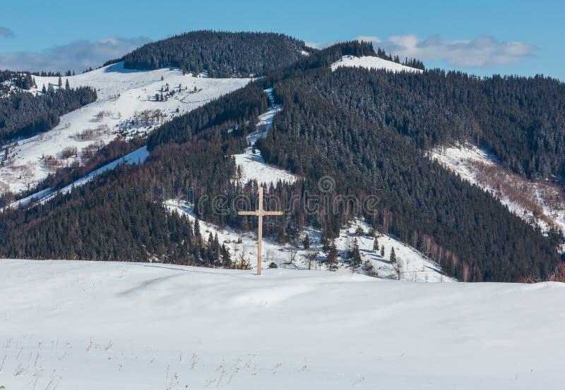 De sneeuw van de ochtendwinter behandelde schilderachtige bergrand en godsdienstig kruis op heuveltopukraine, Karpatische Bergen, royalty-vrije stock fotografie