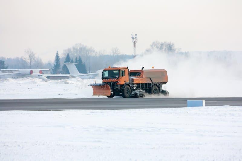 De sneeuw-verwijdering machine maakt de belangrijkste taxibaan bij de luchthaven schoon stock foto's