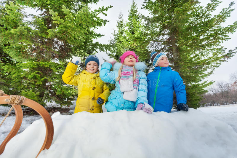 De sneeuwbal van het jonge geitjesspel binnen sneeuwvesting in park stock afbeelding