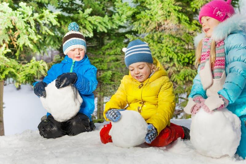 De sneeuwballen van het jonge geitjesbroodje in het park stock afbeeldingen
