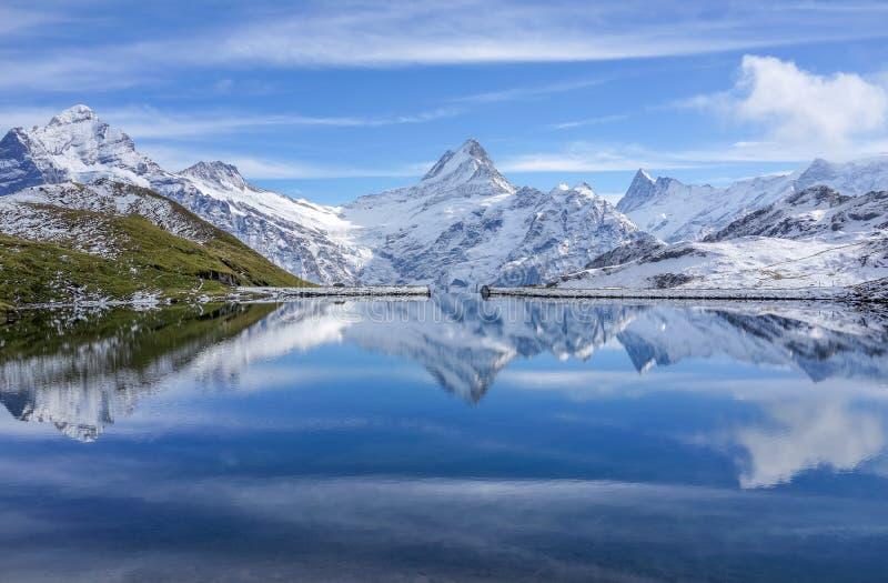 De sneeuwberg met binnen bezinning in meer en duidelijke blauwe hemel stock afbeelding