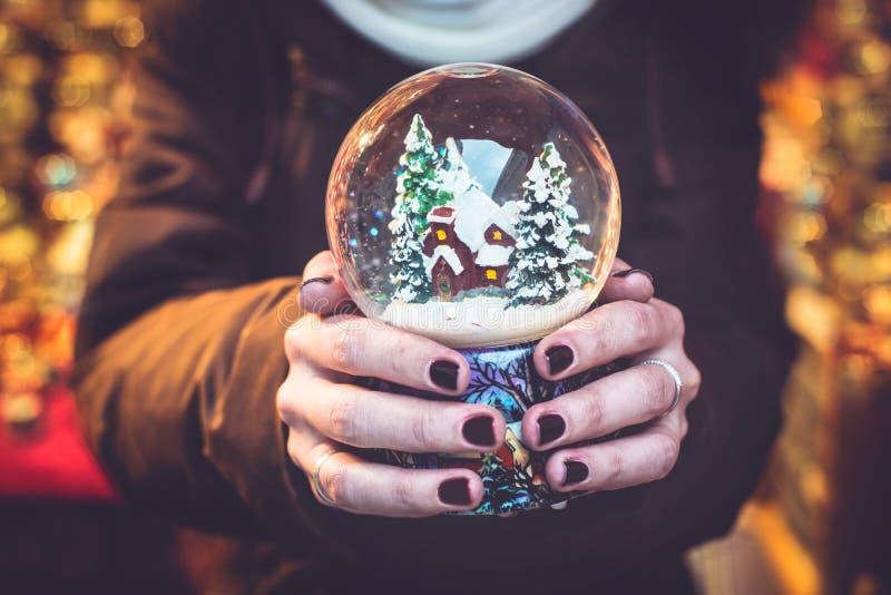 De sneeuwbol van de vrouwenholding op de Kerstmismarkt royalty-vrije stock foto's