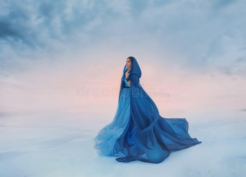 De Sneeuwkoningin in een blauwe regenjas die in de wind fladdert Een reiziger op een achtergrond van zonsopgang of zonsondergang, royalty-vrije stock foto's