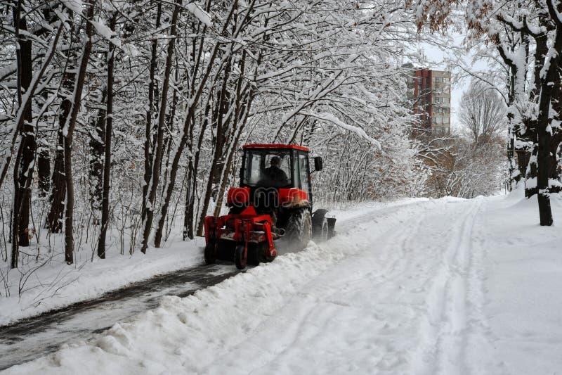 De sneeuwmachine, rode tractor maakt de sneeuw van de sneeuw op de achtergrond van het bos schoon stock afbeeldingen