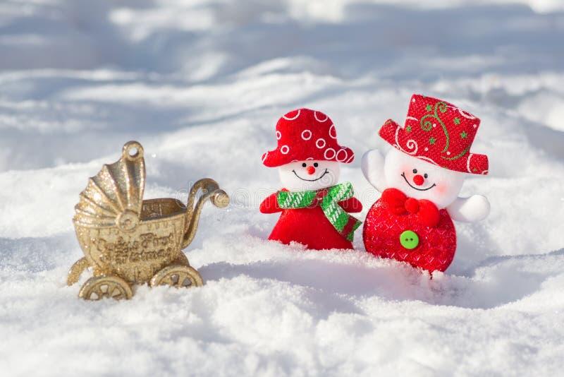 De de sneeuwmanechtgenoot en vrouw zijn prachtig het geklede glimlachen Mijn eerste Kerstmis Om geboorte aan een kind voor Kerstm royalty-vrije stock afbeelding