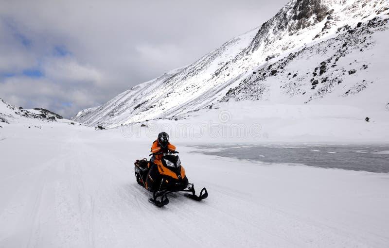 De sneeuwscooter en de vrouw in de bergen stock foto's