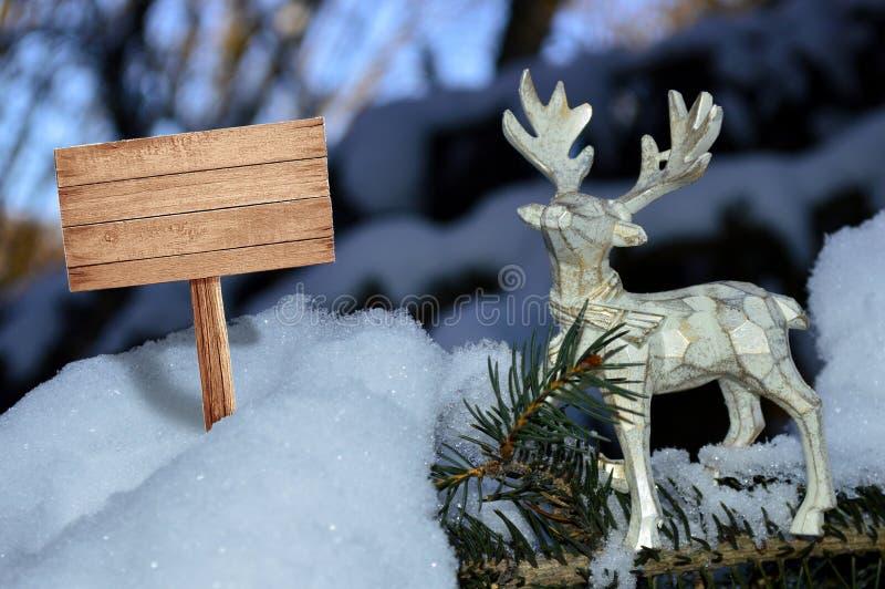 In de sneeuwtribunes een mooi houten hert met een schild voor reclame stock foto