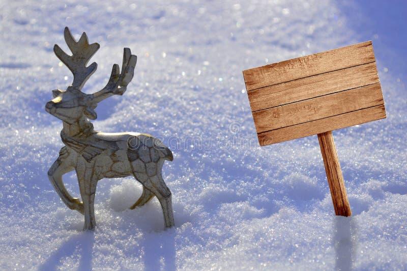 In de sneeuwtribunes een mooi houten hert met een schild voor reclame stock foto's