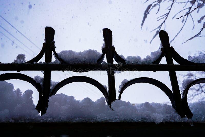 De sneeuwvlokken op gesmede omheining, sluiten stock fotografie
