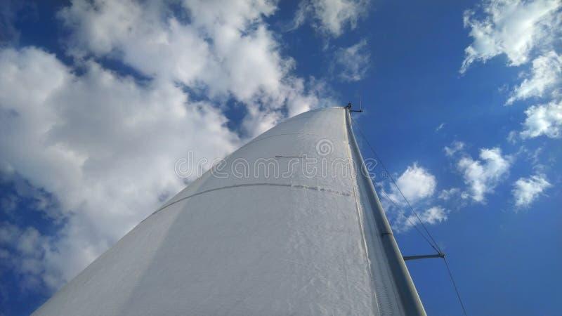 De sneeuwwitte zeilen van het jacht tegen de achtergrond van heldere blauwe hemel en witte wolken royalty-vrije stock foto