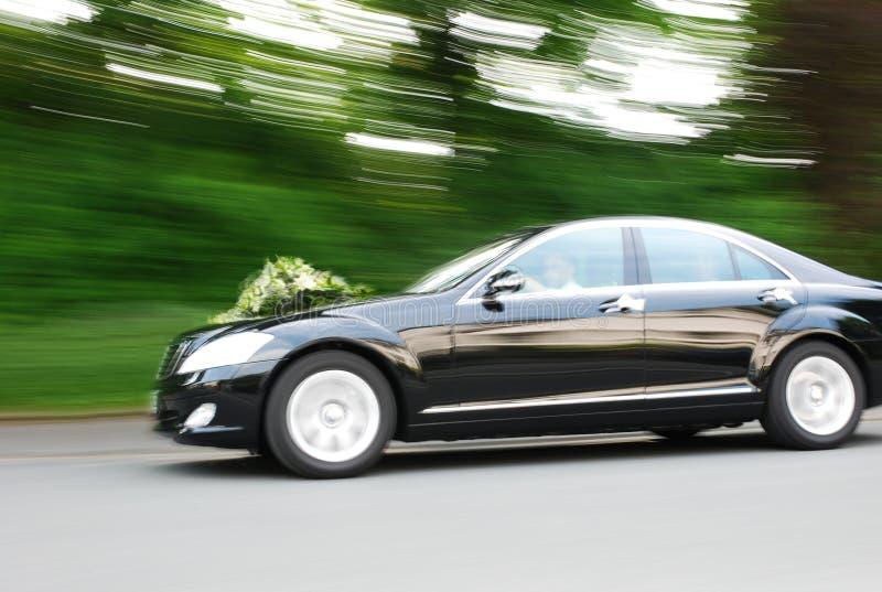 De snel bewegende auto van het huwelijk met boeket op kap