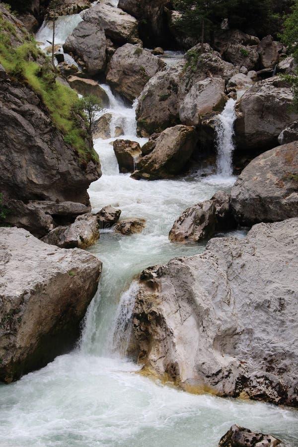 De snelle bergrivier die neer van stenen in Abchazië stroomt stock afbeelding