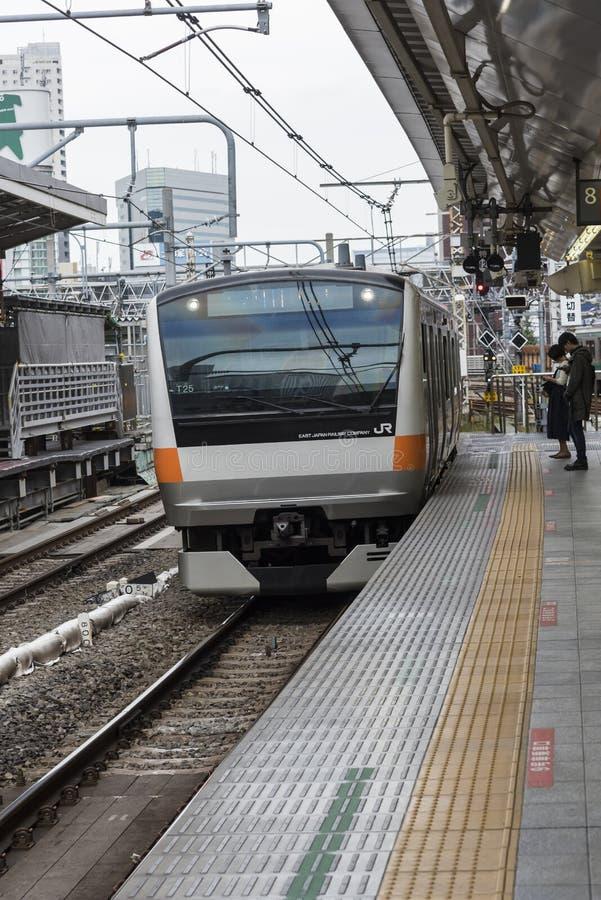 De snelle forenzentrein komt Shinjuku-post Tokyo aan stock afbeelding