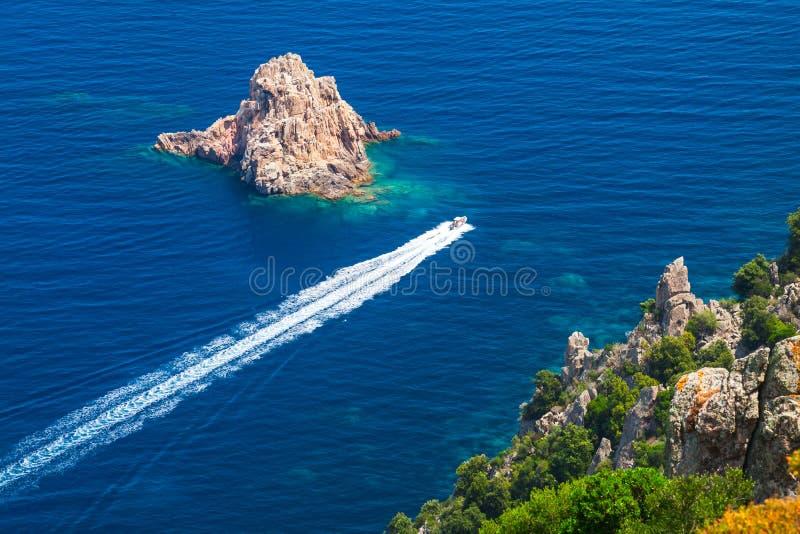 De snelle motorboot gaat tussen de stenen royalty-vrije stock afbeelding