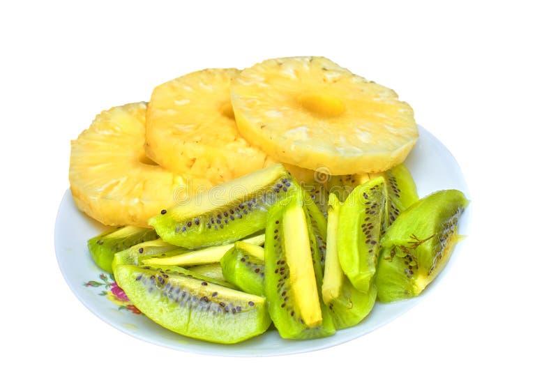 De snijdende ananassen en de kiwi, een plaat van fruit, isoleren op een witte achtergrond stock foto