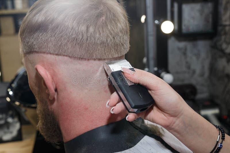 De snijmachine van het kappershaar De meester verstrekt een kapsel royalty-vrije stock foto's