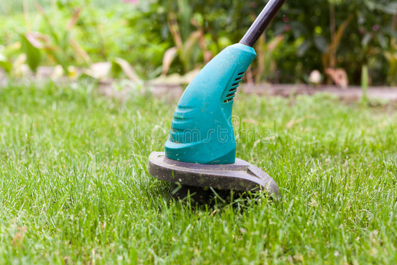 De snoeischaar van het benzinegazon maait sappig groen gras op een gazon op een zonnige de zomerdag Tuinmateriaal stock afbeeldingen