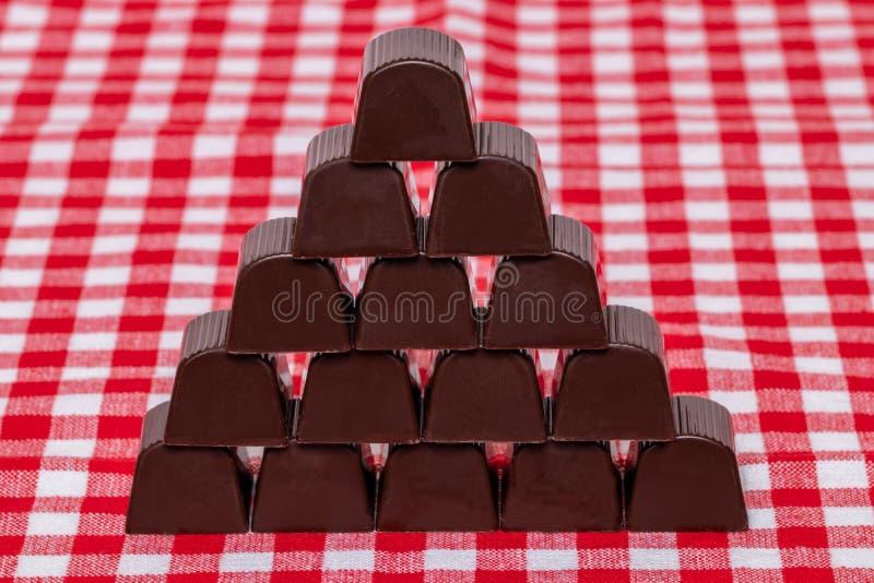 De snoepjes van de chocolade De close-up van piramide maakte van chocoladebanketbakkerij op een rood geruit tafelkleed of servet  royalty-vrije stock afbeeldingen