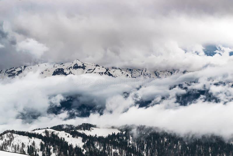 De snow-capped bergen zijn behandeld met dikke wolken stock foto