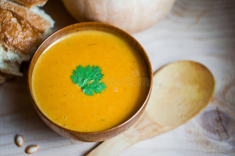 De soep van de Butternutpompoen met eigengemaakt brood op houten achtergrond stock afbeelding