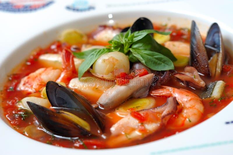 De soep van de tomaat met zeevruchten en vissen stock afbeeldingen
