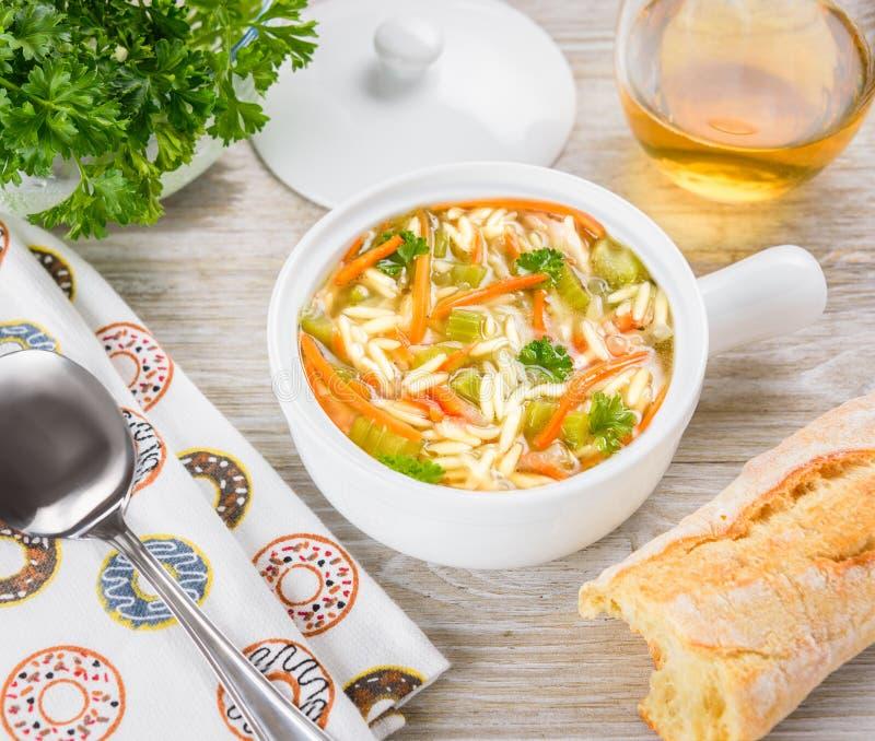 De soep van kippenorzo in een witte slijpstof op houten achtergrond Italiaanse soep met orzodeegwaren royalty-vrije stock afbeelding