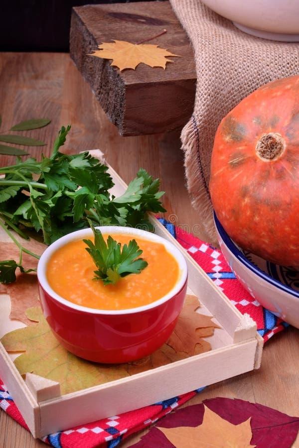 De soep van de pompoenpuree in een gedeelte ceramische kom stock foto's