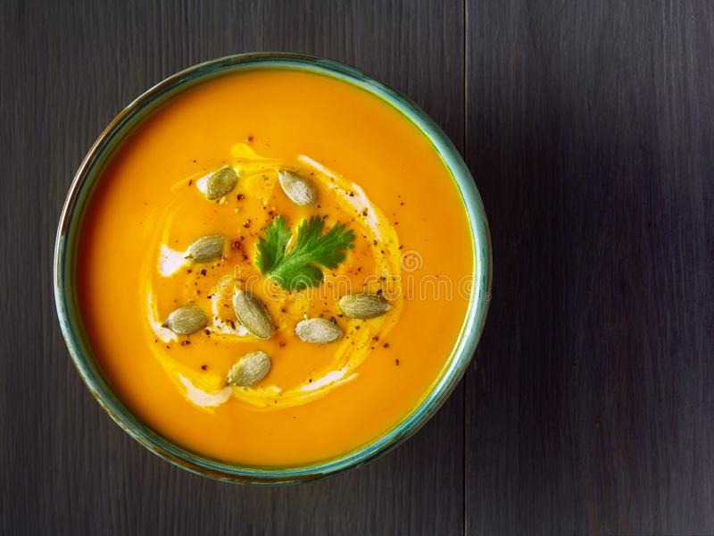 De soep van de pompoenroom in een kom met pompoenzaden, peterselie en room op houten lijst De traditionele herfst, Dankzeggingsma royalty-vrije stock foto
