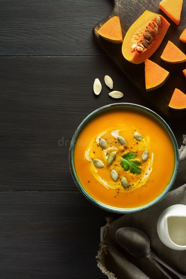 De soep van de pompoenroom in een kom met pompoenzaden, de peterselie, de room en de verse sinaasappel butternut pletten plakken  royalty-vrije stock foto