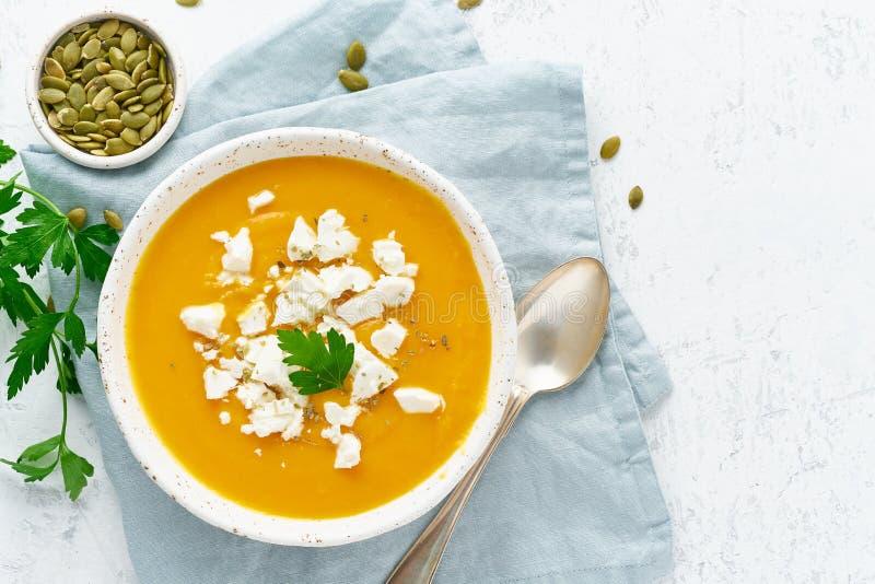 De soep van de pompoenroom met feta-kaas, de herfst eigengemaakt voedsel, witte achtergrond, hoogste mening, exemplaarruimte royalty-vrije stock afbeelding