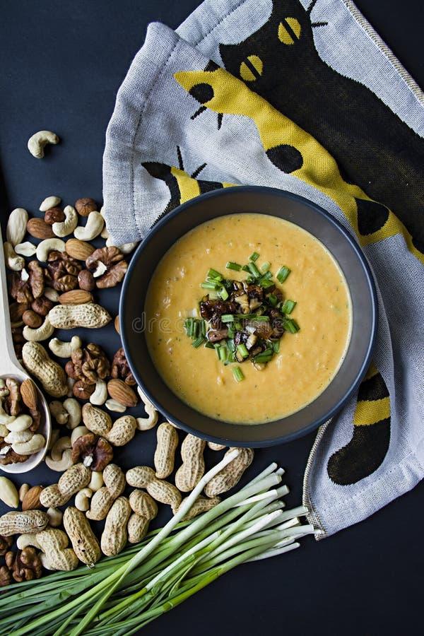 De soep van de pompoenroom met kruiden en noten, in een donkere kom worden gediend die Juist en gezond voedsel Vegetarische schot royalty-vrije stock foto