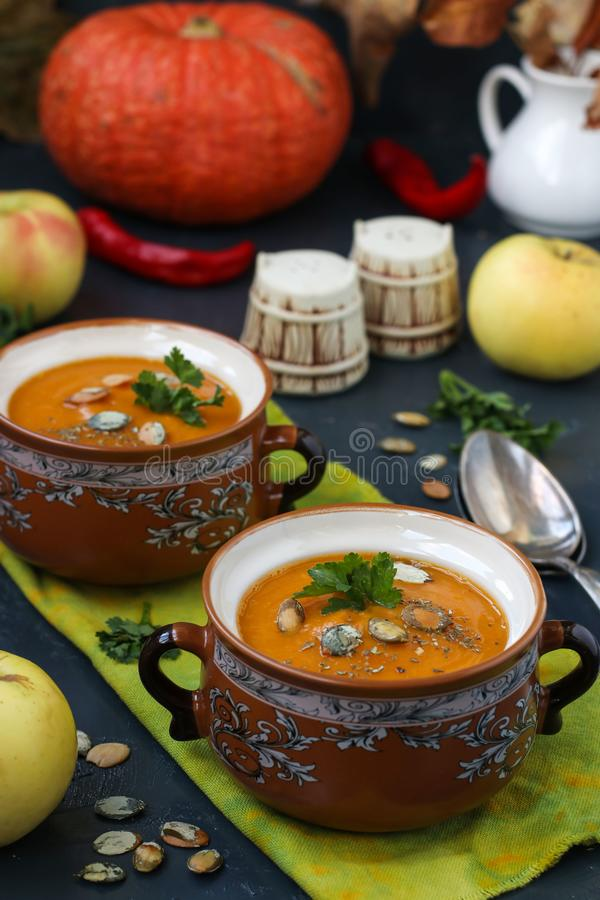 De soep van de pompoenroom in potten tegen een donkere achtergrond stock afbeelding